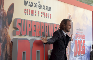 Daniel Ferguson, Director of Superpower Dogs poses on the red carpet of the movie opening.