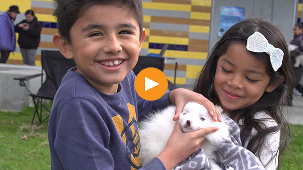 Two young clients are happy with the services provided at their Downtown Dog Rescue Clinic.